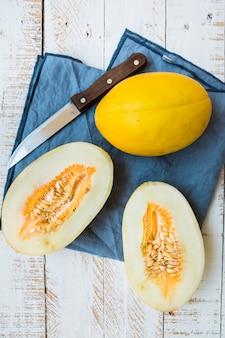 Melón amarillo orgánico maduro, dividido en dos y entero en una mesa de jardín de madera de tablón blanco