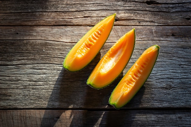 Melón dulce fresco cortado en el tablero de madera. textura de color naranja vista superior .