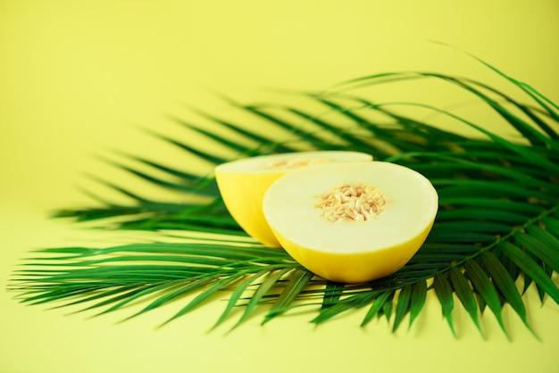 Melón dulce sobre hojas de palma verde tropical. diseño de arte pop, concepto creativo de verano. comida vegana cruda.