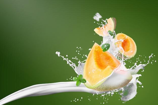 Melones japoneses y salpicaduras de leche aislado sobre fondo verde