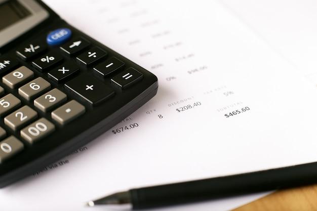 Membrete de factura con calculadora y bolígrafo, papel financiero y herramientas de oficina
