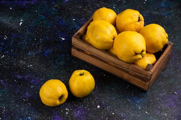 Membrillos enteros maduros en caja de madera sobre mesa oscura.