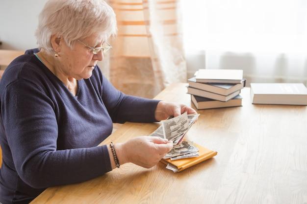 Memoria. eldery mujer mirando fotos vintage.