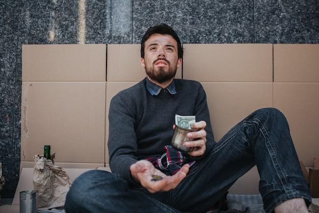 Mendigo adulto está sentado en cartón y pidiendo dinero