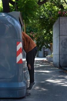 Mendigo mirando a través de contenedores de basura en las calles