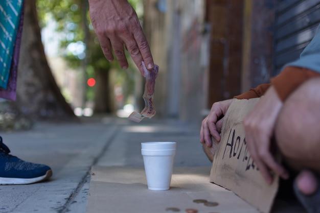 Mendigo recibiendo dinero de un extraño