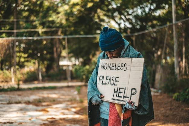 Los mendigos se paran en la calle con mensajes para personas sin hogar, por favor ayuda.