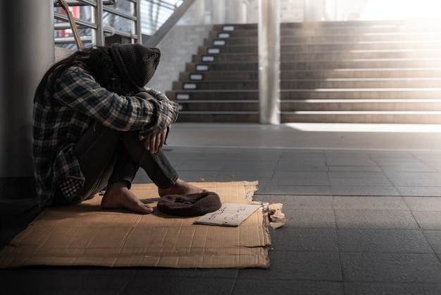 Mendigos, personas sin hogar sentados en el piso acérquese a la prohibición, pida una fracción del dinero