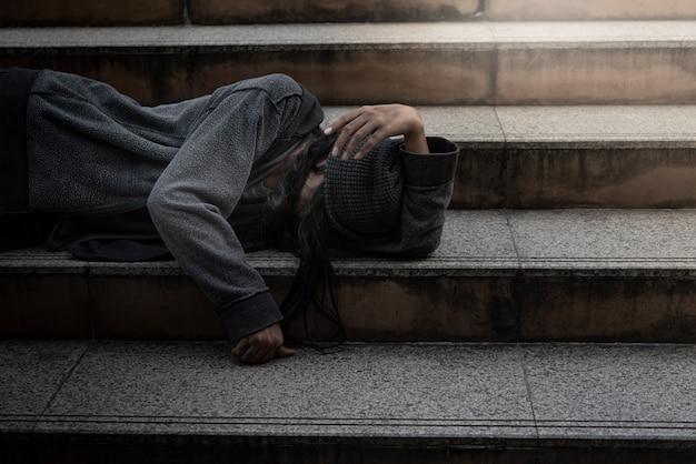 Mendigos, personas sin hogar, tumbados en los escalones, piden una fracción del dinero.