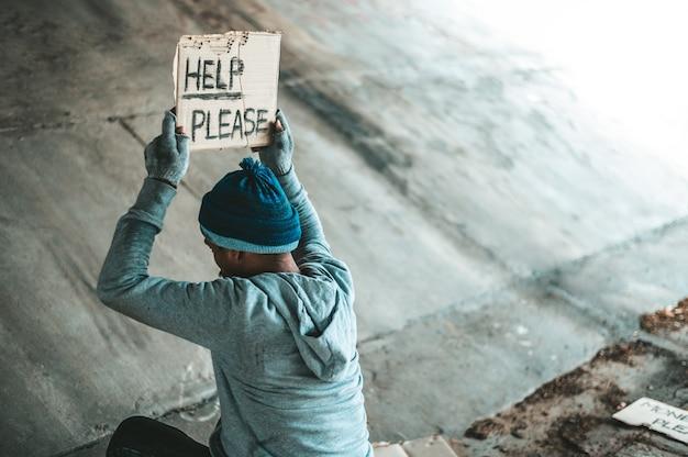Mendigos sentados debajo del puente con un cartel, ayuda por favor.
