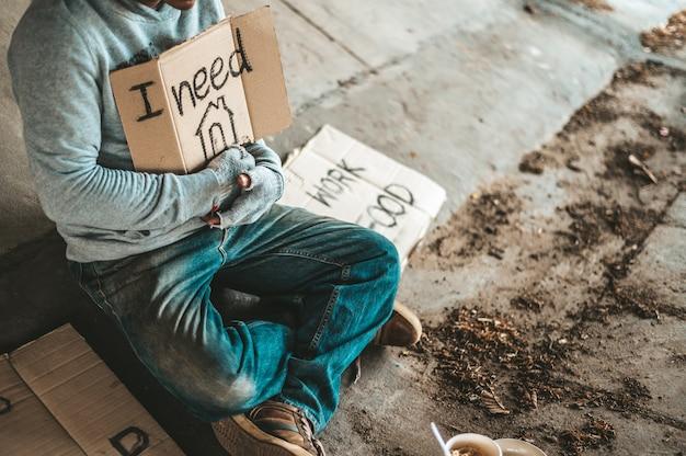 Mendigos sentados debajo del puente con un cartel, por favor, a casa.
