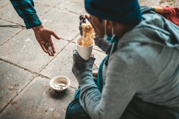 Los mendigos se sentaron envueltos en paños y comiendo fideos.