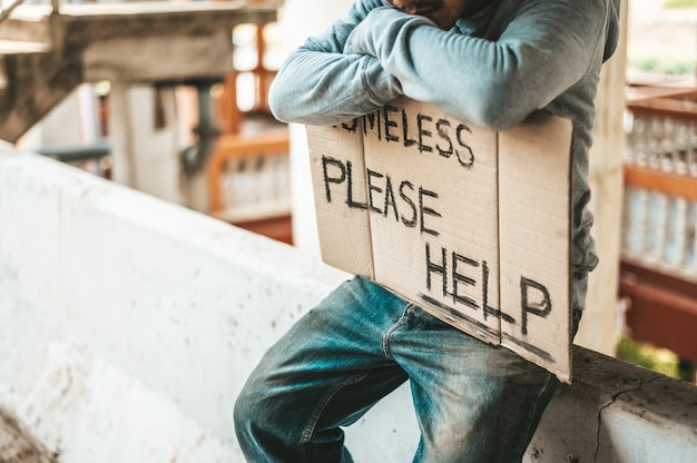 Los mendigos se sientan en las barreras con personas sin hogar. por favor, mensajes de ayuda.