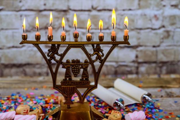 Menorah de bronce de hanukkah con las velas ardientes en el viejo vintage del frente de la tabla de madera