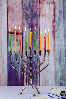 Menorah de hanukkah con las velas encendidas en el viejo vintage del frente de la tabla de madera
