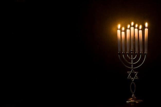 Menorah judía de hanukkah en espacio negro de la copia