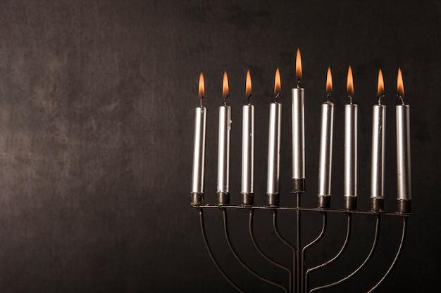 Menorah con velas cerca de la pared gris
