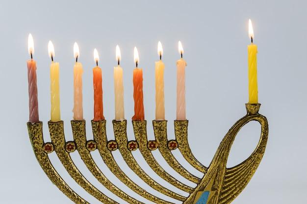 Menorah con velas encendidas en celebración de janucá. una vela simbólica encendida para la festividad judía