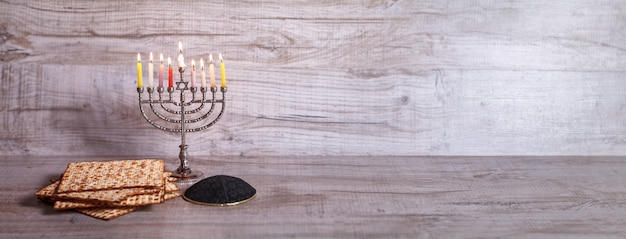 Menorah con velas encendidas, kipá y matzá para hanukkah