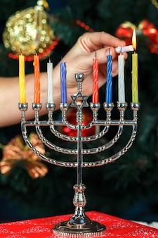 Menorah con velas para hanukkah en el fondo del árbol de año nuevo
