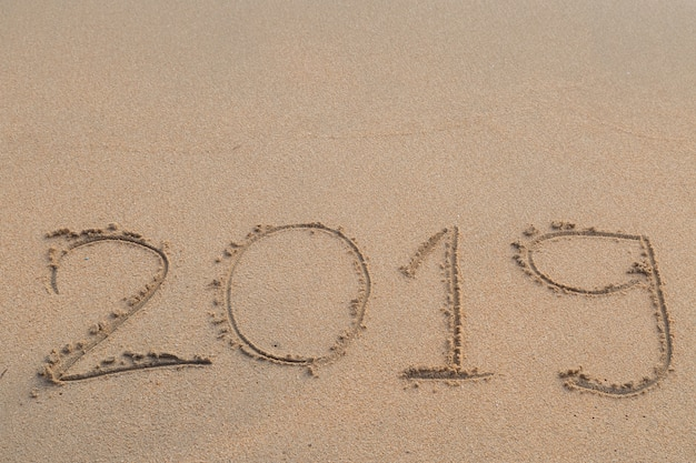 Mensaje abstracto año 2019 escrito en el fondo de arena de la playa