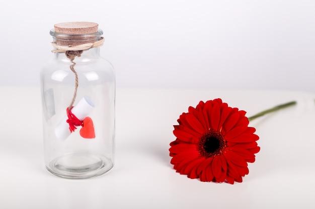 Mensaje de amor en una botella. rollo de papel blanco con hilo rojo y gerbera roja flor sobre un fondo blanco. concepto de día de san valentín