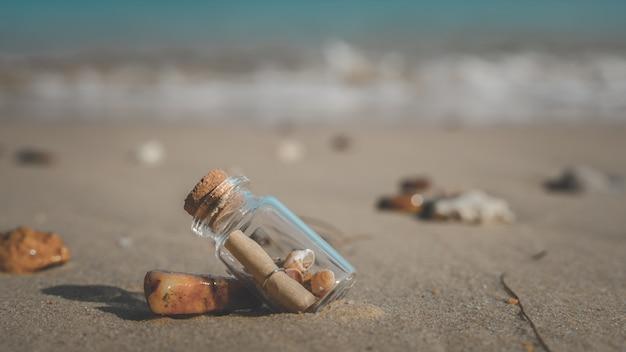 Mensaje en botella en la playa de arena