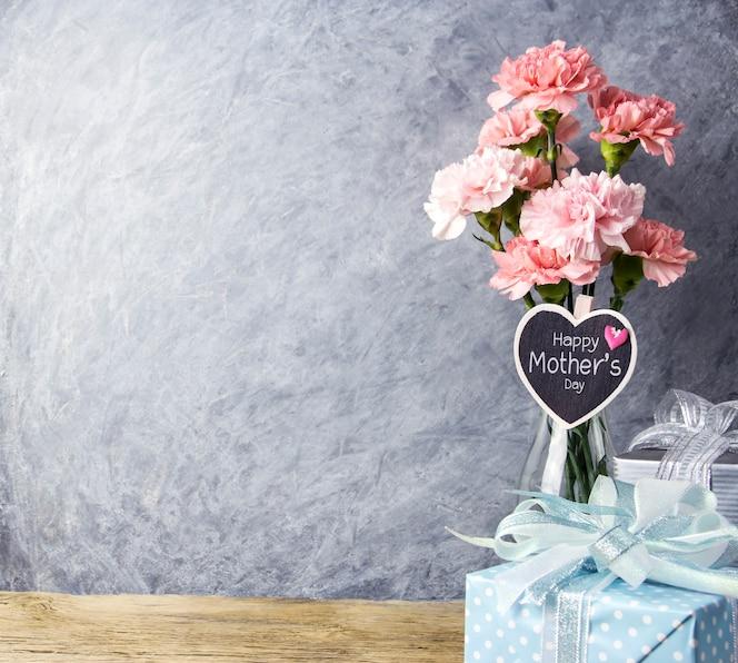 Mensaje del día de las madres feliz en madera de corazón y flor de clavel rosa