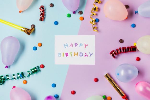 Mensaje de feliz cumpleaños en azul y rosa rodeado de serpentinas; gemas y globos sobre fondo de color