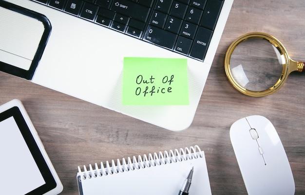 Mensaje fuera de la oficina en una nota adhesiva con la computadora.