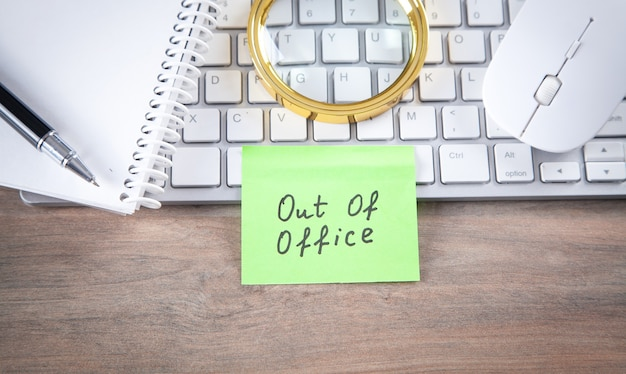 Mensaje fuera de la oficina en nota adhesiva con teclado de computadora, mouse, bloc de notas.