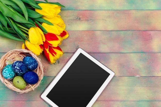 Mensaje en la pantalla de la tableta y coloridos tulipanes y huevos de pascua en madera