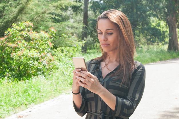 Mensaje que mecanografía enfocado de la señora del negocio en smartphone