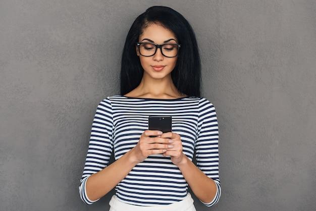 Mensaje rápido a un amigo. atractiva mujer africana joven sosteniendo un teléfono inteligente y mirándolo mientras está de pie contra el fondo gris