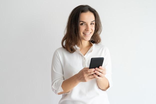 Mensaje sonriente alegre de la muchacha que manda un sms o que disfruta de la nueva aplicación.