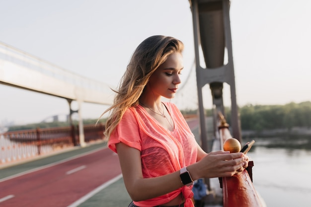Mensaje de texto de chica rubia pensativa mientras está de pie cerca del camino de ceniza. hermosa mujer en ropa casual posando al aire libre después del entrenamiento.