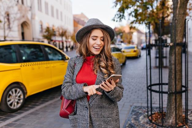 Mensaje de texto de mujer de negocios guapa mientras camina por la calle