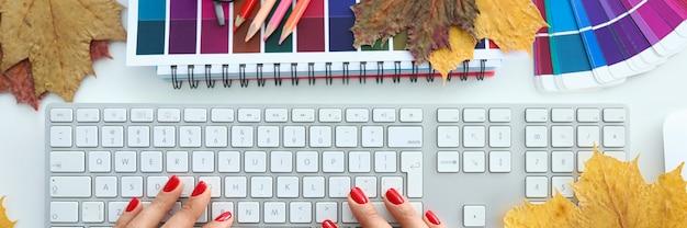 Mensaje de texto de tipo de mano femenina con teclado blanco en primer plano de la mesa de oficina. concepto de educación empresarial profesional de otoño