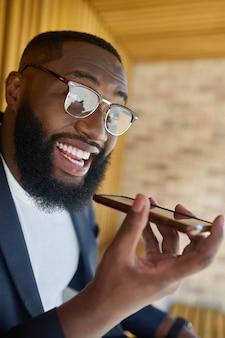 Mensaje de voz. un hombre negro en anteojos grabando un mensaje de voz.