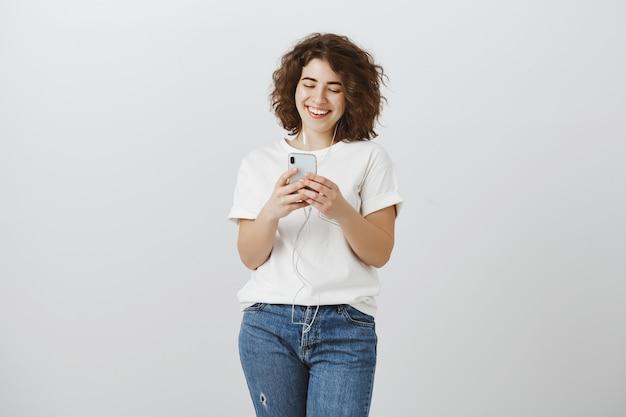 Mensajería chica atractiva sonriente, mirando feliz en la pantalla del teléfono móvil
