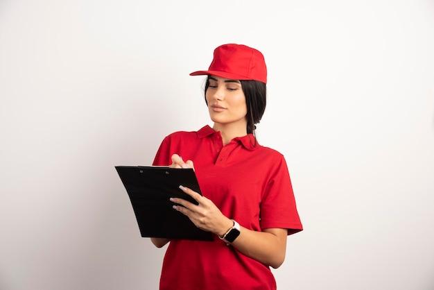 Mensajería femenina escribiendo órdenes en el portapapeles. foto de alta calidad