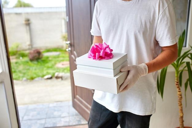 Mensajería hombre entrega sin contacto presenta, caja de regalo durante una epidemia de coronavirus.