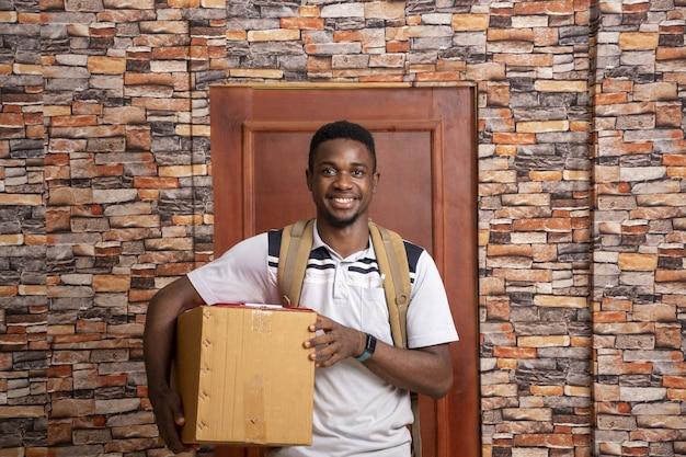 Mensajero africano joven sonriente sosteniendo un paquete de pie delante de una puerta