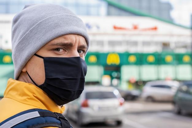 Mensajero de alimentos con máscara médica negra en el estacionamiento. servicio de comida a domicilio