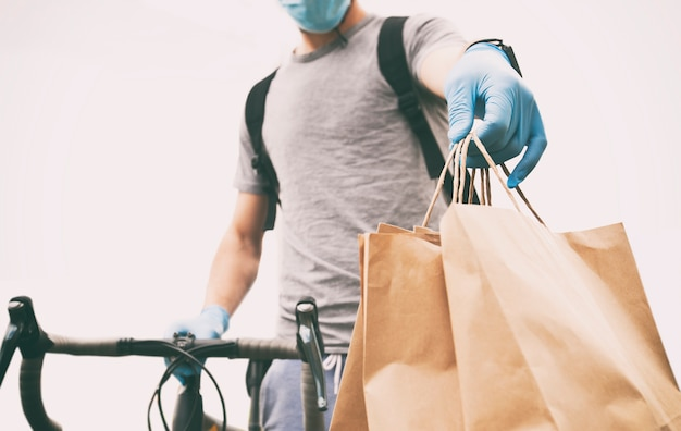 Mensajero en bicicleta está entregando bolsa de papel con orden a persona