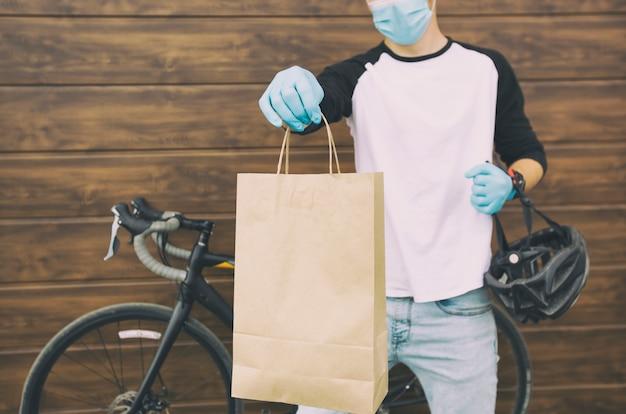 El mensajero en la bicicleta está entregando la bolsa de papel con orden a la persona