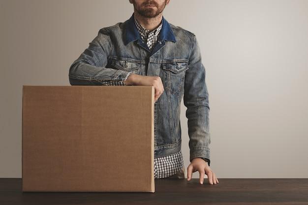 Mensajero brutal barbudo con chaqueta de trabajo de jeans permanece cerca de la caja de papel de cartón grande presentada con productos en la mesa de madera.
