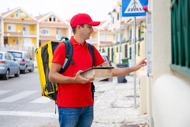 Mensajero caucásico llevando el paquete y llamando al timbre mientras realiza la entrega a domicilio. repartidor de mediana edad con bolsa térmica amarilla de pie delante de la casa. servicio de entrega y concepto de correo.