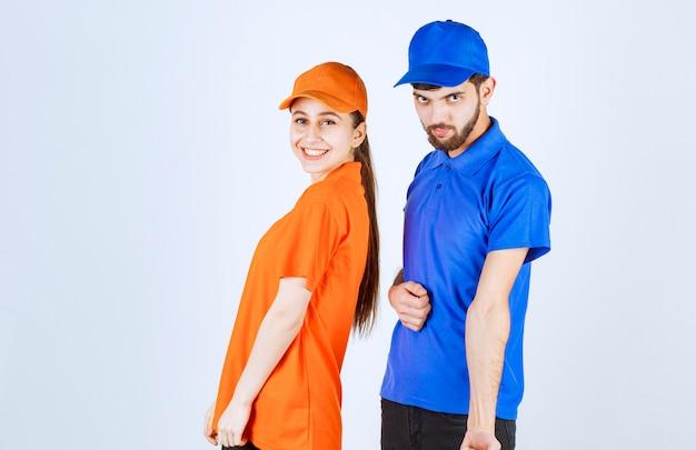 Mensajero chico y chica con uniformes azules y amarillos dando poses encantadoras y alegres.