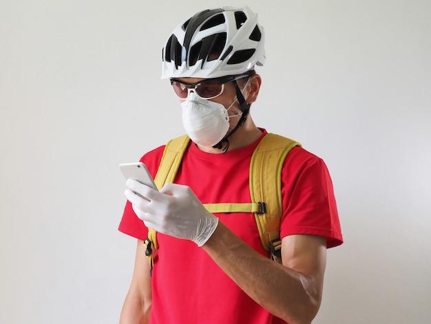 Mensajero ciclista en casco, máscara protectora y guantes médicos, mirando el teléfono inteligente